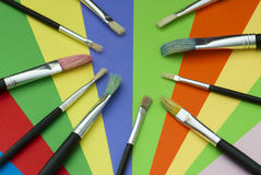 Brushes and colored paper Stock Images