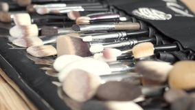 Set of brushes for makeup scattered on wooden background. Various makeup brushes on wooden table. Tools for makeup atrist stock video footage