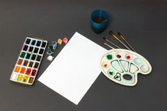 A set of brushes on a white sheet. Set of drawing, paint, brushes, glass, on a white background Stock Images