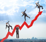 Set of businessmen trying not to fall from arrow Stock Photos
