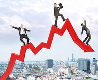 Set of businessmen trying not to fall from arrow Royalty Free Stock Images