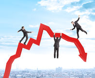 Set of businessmen trying not to fall from arrow Stock Images