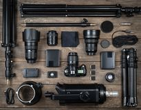 Set of the camera and photography equipment lens, tripod, filter, flash, memory card, hard desk, reflector on wood desk. Royalty Free Stock Image