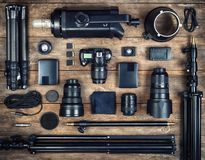Set of the camera and photography equipment  tripod, filter, fl. Ash, camera lens, memory card, hard desk, reflector on wood desk. Professional photographer royalty free stock photography