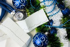 Set of cardiac diagnostic instruments with  Christmas or New Year decorations. Stethoscope and pulse trace ECG tape lying near art Stock Photos