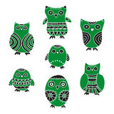 Set of cartoon green and black owls and owlets on a white background Royalty Free Stock Photo