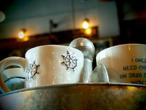 Set of Mugs in a Retro Coffee Shop. A set of ceramic mugs on a tin shelf in a retro, vintage style coffee shop royalty free stock photos