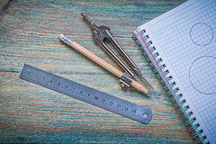 Set of checked copybook ruler pair of compasses pencil on vintag Royalty Free Stock Photo