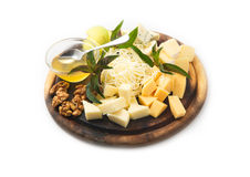 Set of cheese with honey and nuts on a round wooden tray Royalty Free Stock Images