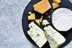 A set of cheeses: brie, blue cheese, parmesan, camembert on a slate board. Plate with delicacies. View from above. A set of cheeses: brie, blue cheese, parmesan royalty free stock photos