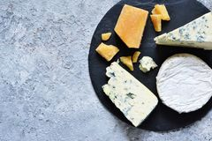 A set of cheeses: brie, blue cheese, parmesan, camembert on a slate board. Plate with delicacies. View from above. A set of cheeses: brie, blue cheese, parmesan royalty free stock images