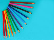 A set of children`s, colored pencils on a turquoise background. stock photography