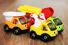 A set of children`s toy cars, construction machinery. On wooden background Stock Photos