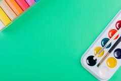 A set of children`s watercolors to a set of plasticine on a green background Stock Photos