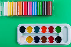 A set of children`s watercolors to a set of plasticine on a green background Royalty Free Stock Photography