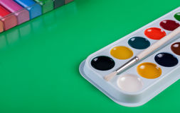 A set of children`s watercolors to a set of plasticine on a green background Royalty Free Stock Photo
