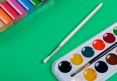 A set of children`s watercolors to a set of plasticine on a green background Stock Image