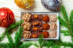 Set of chocolates. Truffles with almonds, coconut and cookie crumbs. In a box on an old white table with fir branches. Gift for Christmas and New year. Gourmet royalty free stock photos