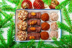 Set of chocolates. Truffles with almonds, coconut and cookie crumbs. In a box on an old white table with fir branches. Gift for Christmas and New year. Gourmet royalty free stock photo