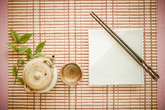 Set chopsticks and dish with Asian teapot and tea cup on wooden. Royalty Free Stock Images