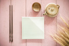 Set chopsticks and dish with Asian teapot and tea cup on wooden. Royalty Free Stock Photo