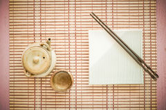Set chopsticks and dish with Asian teapot and tea cup on wooden. Stock Image