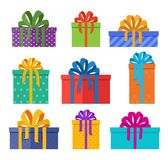 Set of christmas gifts boxes in holiday packages with colored bowknots. Christmas presents designed in flat style. Royalty Free Stock Photo