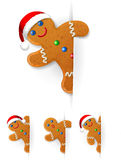 Set of Christmas gingerbread mans. Looks out from a vertical white paper sheet Royalty Free Stock Photography