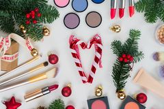 Christmas make up cosmetics. Set of Christmas make up cosmetics products with evergreen tree flat lay styled scene Stock Images