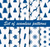 Set of Christmas seamless patterns with fir-trees, deer and celebratory symbols. Ten winter backgrounds. Vector Stock Images