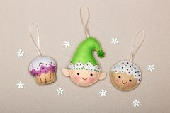 Set of Christmas tree decorations, cake, elf, cookies, handmade of felt from a beige background with snowflakes stock photography