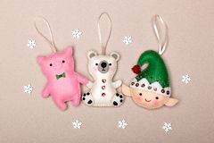 Set of Christmas tree decorations, piggy, polar bear, elf, handmade from felt on a beige background with snowflakes stock photos