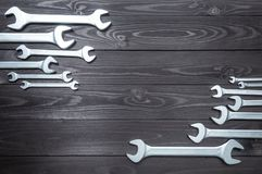 Set of chromed wrenches on a dark wooden workbench. top view, copy space stock image