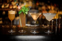 Set of classic cocktails: Dirty Martini, Sherry Cobbler, Brandy Crusta and Margarita. Arranged on the bar counter stock photo