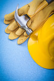 Set of claw hammer safety gloves building helmet on blue backgro Royalty Free Stock Photo