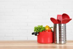 Set of clean cookware, utensils and vegetables on table against white brick wall. Space for text stock photos