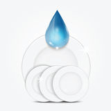 Set of clean dishes and blue drop. Dishwashing liquid on the background plates Royalty Free Stock Photography
