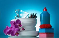 Set of clean dishes and Orchid flower, detergent, sponge, on blue. Background Royalty Free Stock Images