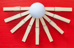 Set of  cloth pegs and golf ball on wooden red desk. Set of  cloth pegs and golf ball on wooden red table Stock Images