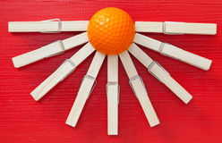 Set of  cloth pegs and golf ball on wooden red desk. Set of  cloth pegs and golf ball on wooden red table Royalty Free Stock Photo