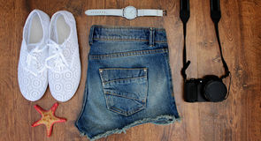 Set clothes for going to sea: jeans shorts, sneakers, watches, photocamera, shells, a top view of  wooden background Stock Photo