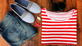 Set clothes for going to sea: jeans shorts, a striped shirt and  sneakers, photocamera, shells,  top view of  wooden Stock Photos