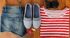 Set clothes for going to sea: jeans shorts, a striped shirt and striped sneakers, photocamera, shells, a top view of a wooden back Stock Image