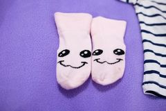 Pair of small and cute baby socks. Set of clothes of an infant baby including skirt tshirt socks and a small toy stock photography