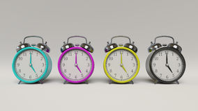 A set of CMYK Retro Styled Alarm Clocks. Line of four retro styled alarm clocks in cyan, magenta, yellow, and key, shot in a clean white studio environment. This Stock Photos