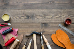 Set of cobbler tools on brown wooden desk background top view copyspace stock photography