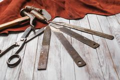 Set of cobbler tools on the light wooden background. Space for t. Set of cobbler tools on a light wooden background. Space for text stock image