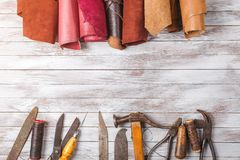 Set of cobbler tools and a lot of brightly colored leather in rolls on wooden background. Space for text. Set of cobbler tools and a lot of brightly colored royalty free stock photography