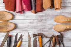 Set of cobbler tools and a lot of brightly colored leather in rolls on wooden background. Space for text. Set of cobbler tools and a lot of brightly colored royalty free stock images