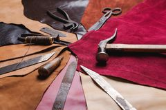 Set of cobbler tools on a pieces of colorful leather. Set of cobbler tools on pieces of colorful leather close up royalty free stock image